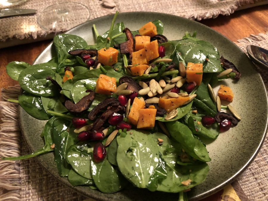 A warm wilted spinach salad topped with mushroom bacon, sweet potatoes, and pumpkin and pomegranate seeds